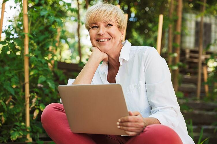 smiling-business-woman-working-remotely-with-laptop-outside-surrounded-by-trees