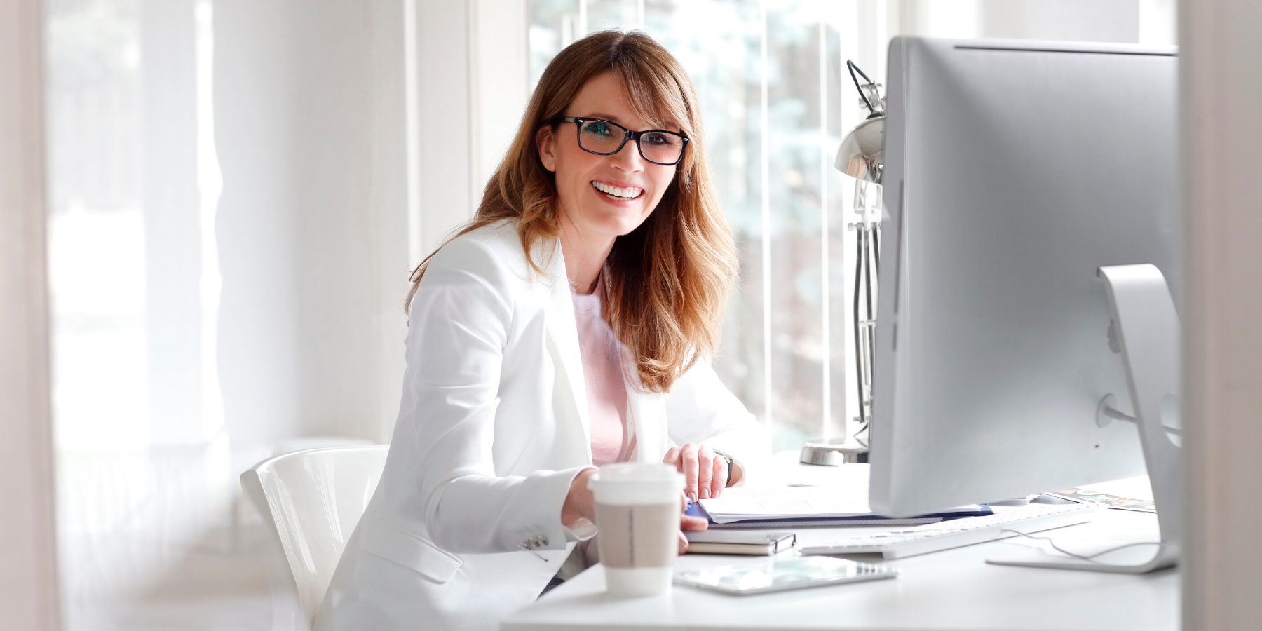 accounts_payable_business_woman_in_white_sittiing_at_computer_with_coffee