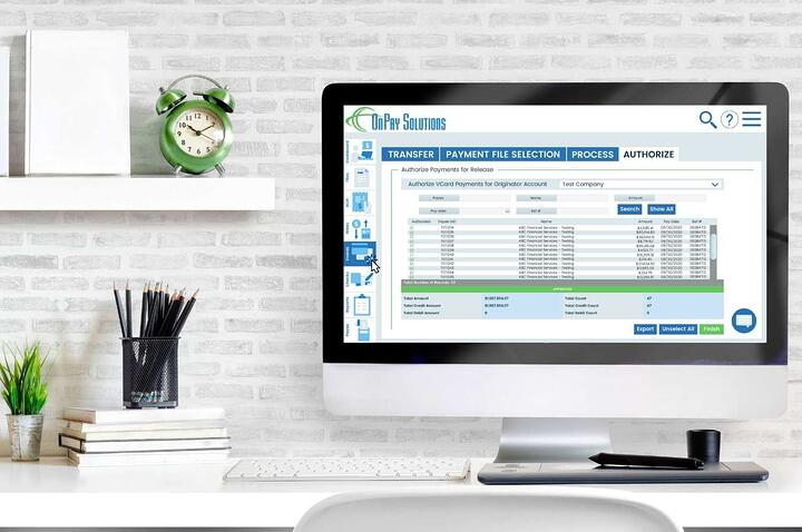 Desktop computer at a home desk with OnPay Solutions Payment Automation on the screen