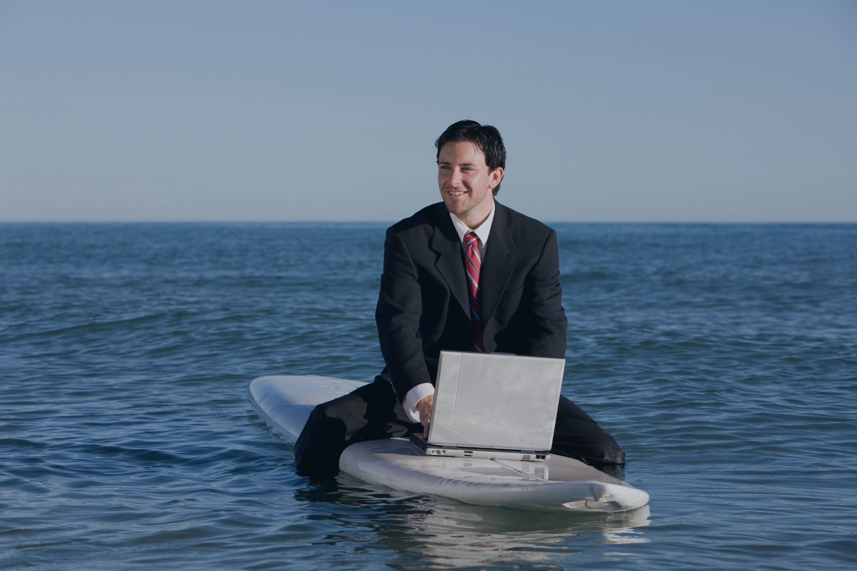 Business_man_sitting_on_a_surfboard_in_the_ocean_smiling_and_typing_on_a_laptop_working_vacation