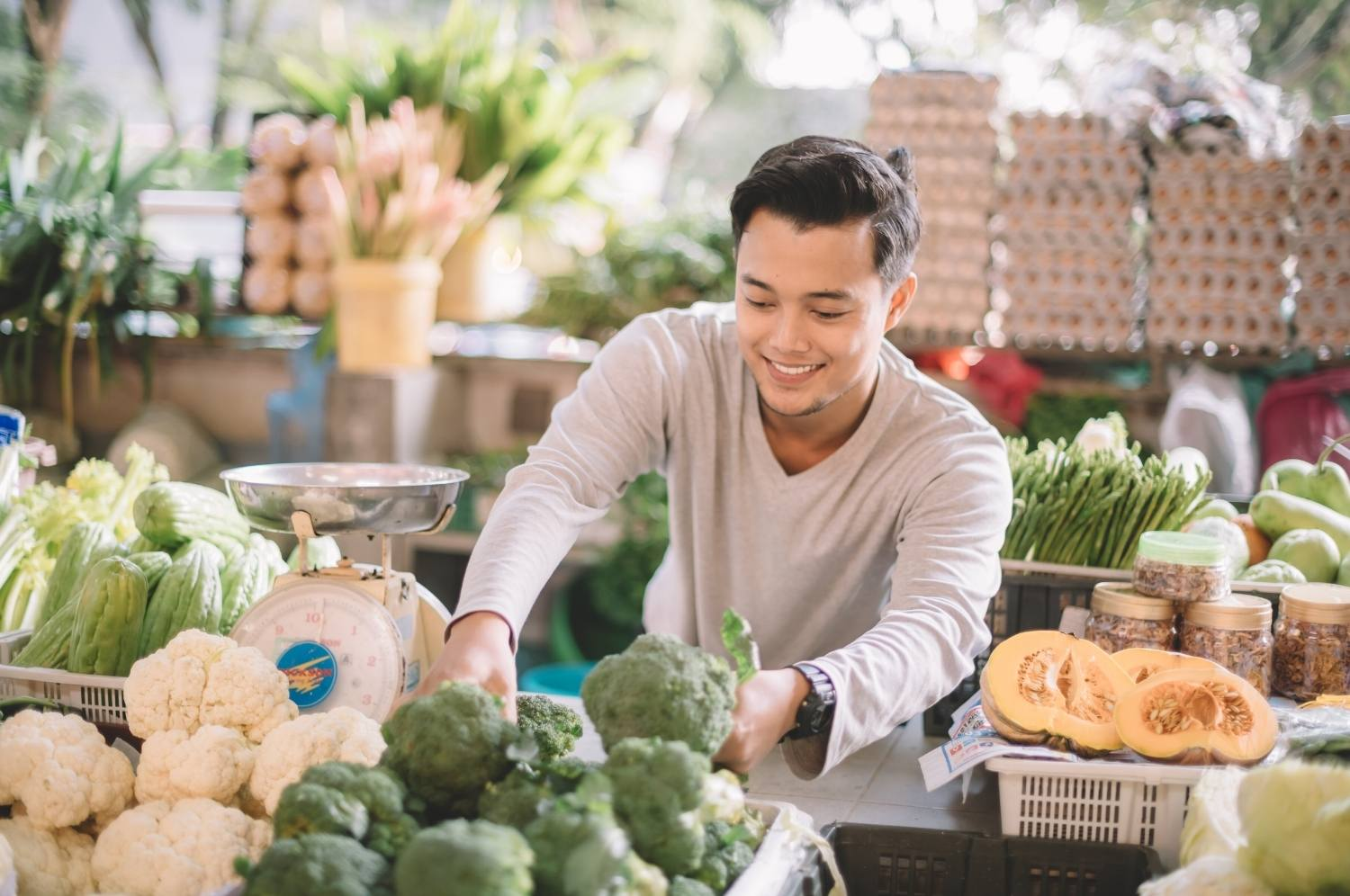 Happy grocery owner arraging his vegtables getting ready to open business