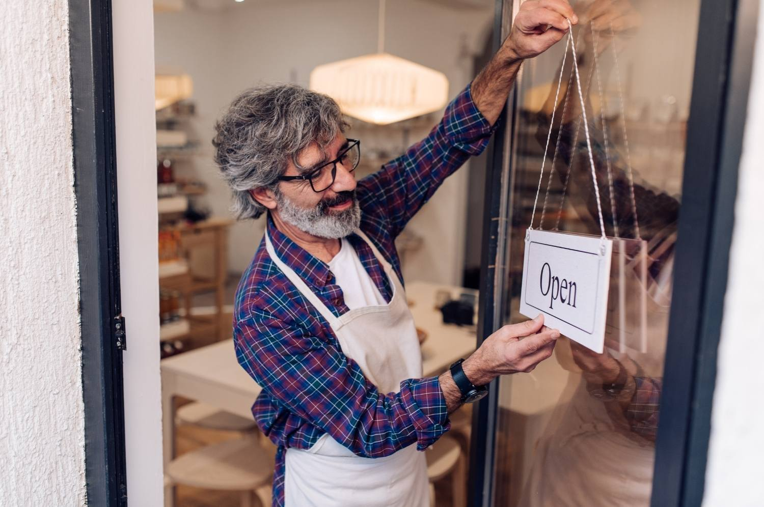 Satisfied, smiling retail owner opening his store