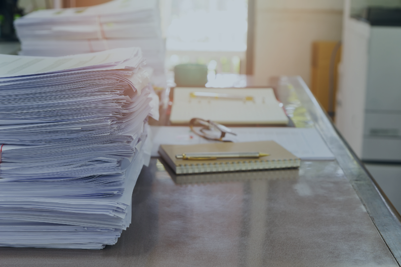 business_desk_burdened_with_stacks_of_paper_with_a_notepad