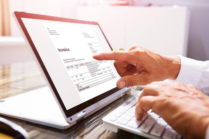 businessmans hands working on electronic invoice on laptop