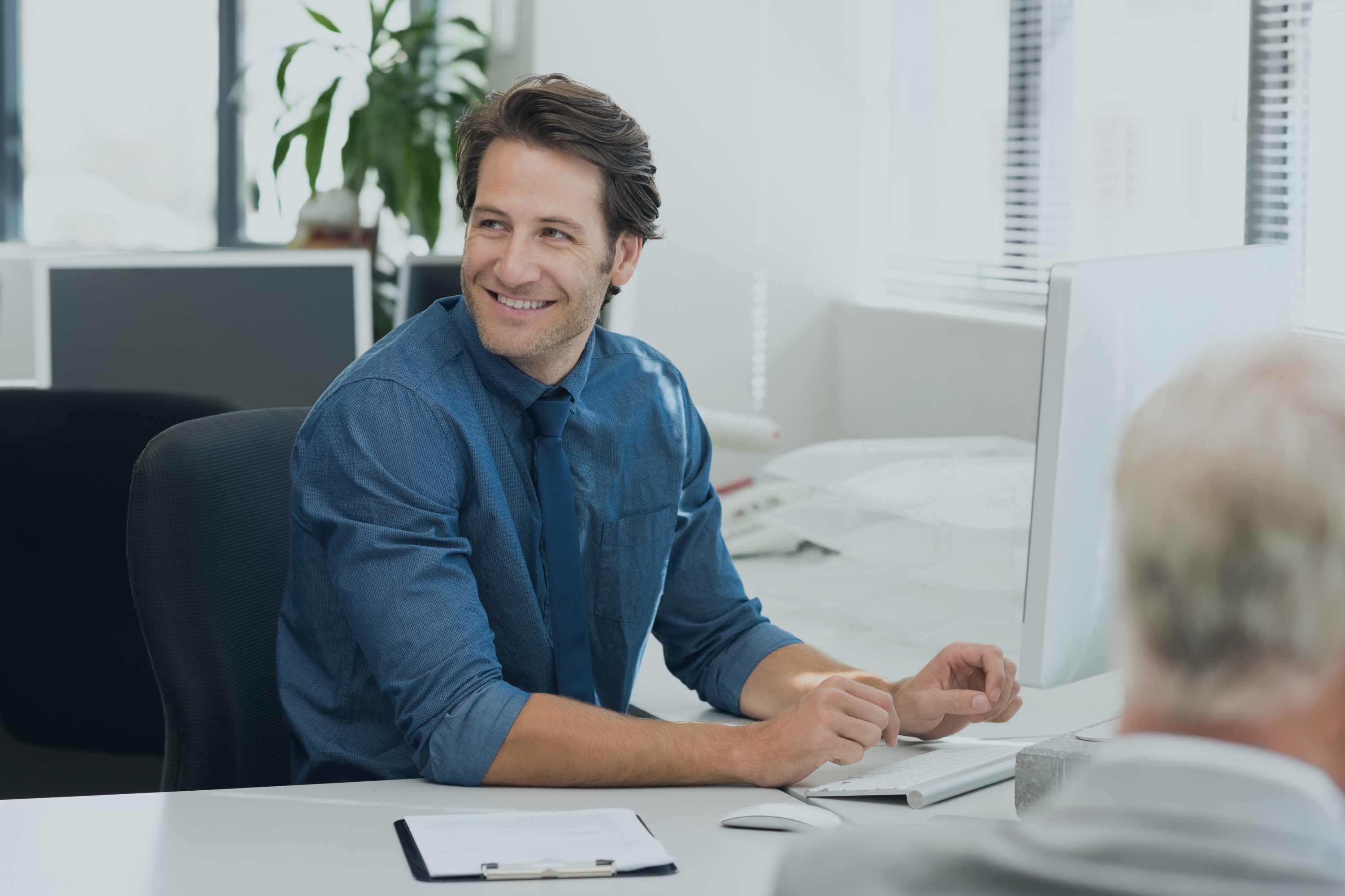 cheerful-youn-ap-manager-businessman-working-on-desktop-computer-at-office