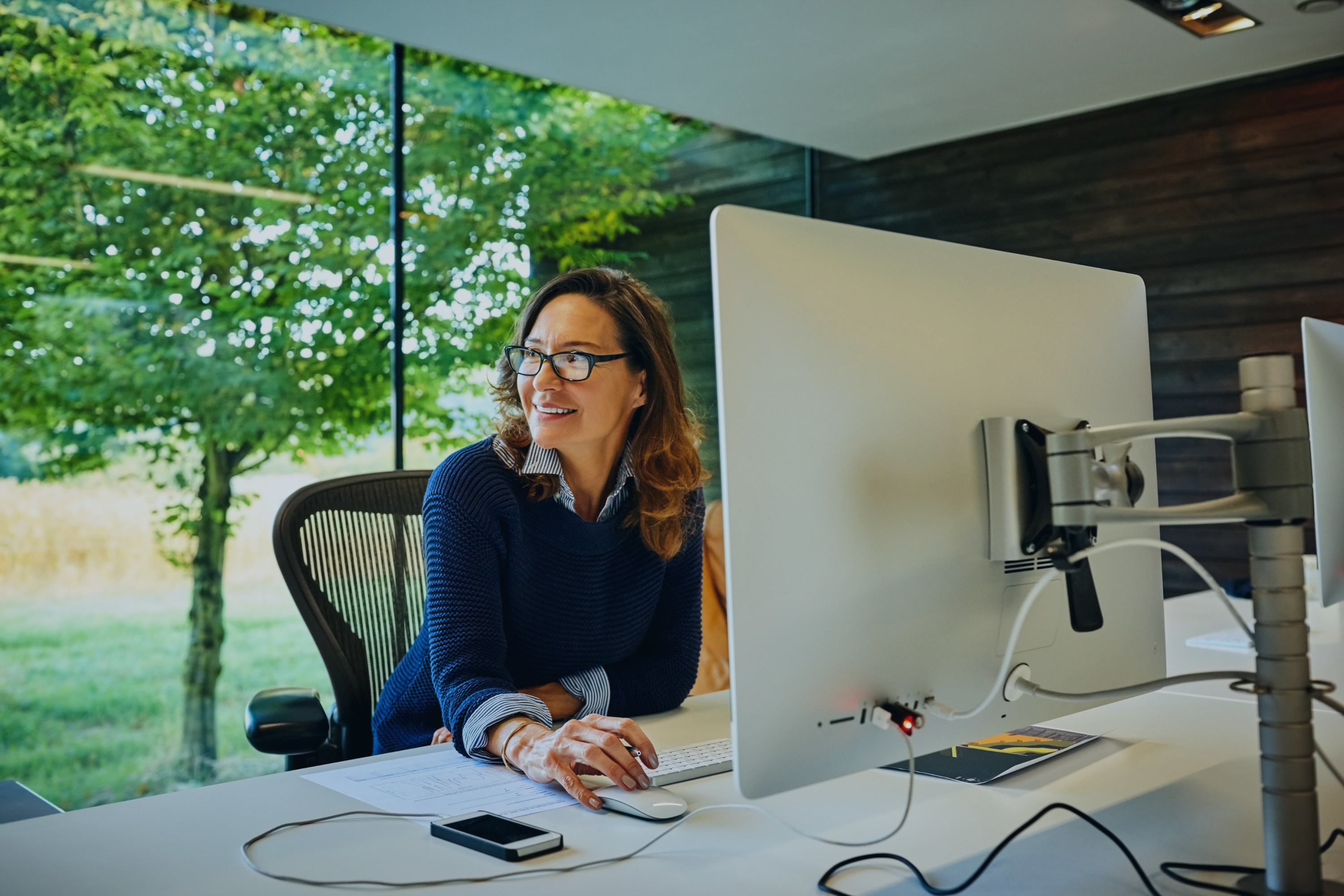 happy-mature-ap-businesswoman-sitting-at-her-desk