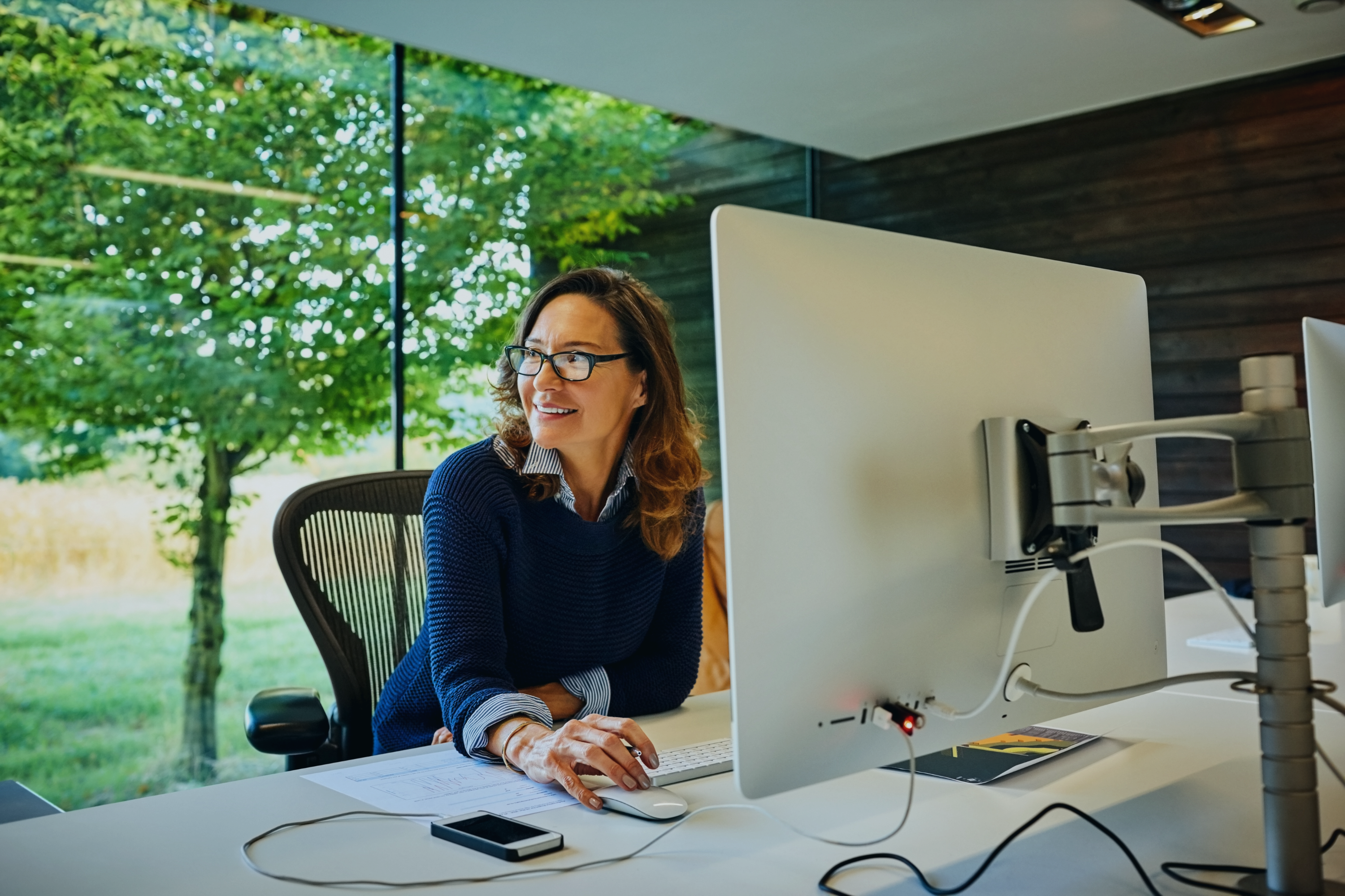 indoor-shot-of-happy-mature-finance-businesswoman-sitting-at-her-deak-and-looking-away-in-office
