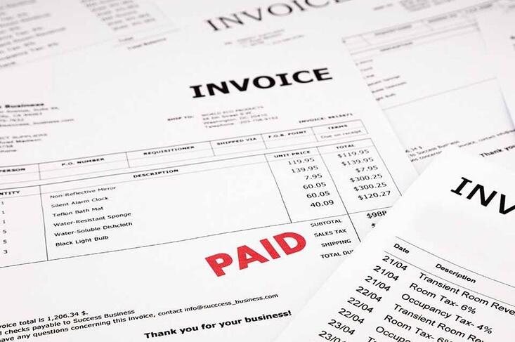 stack of invoices with paid stamped on the top