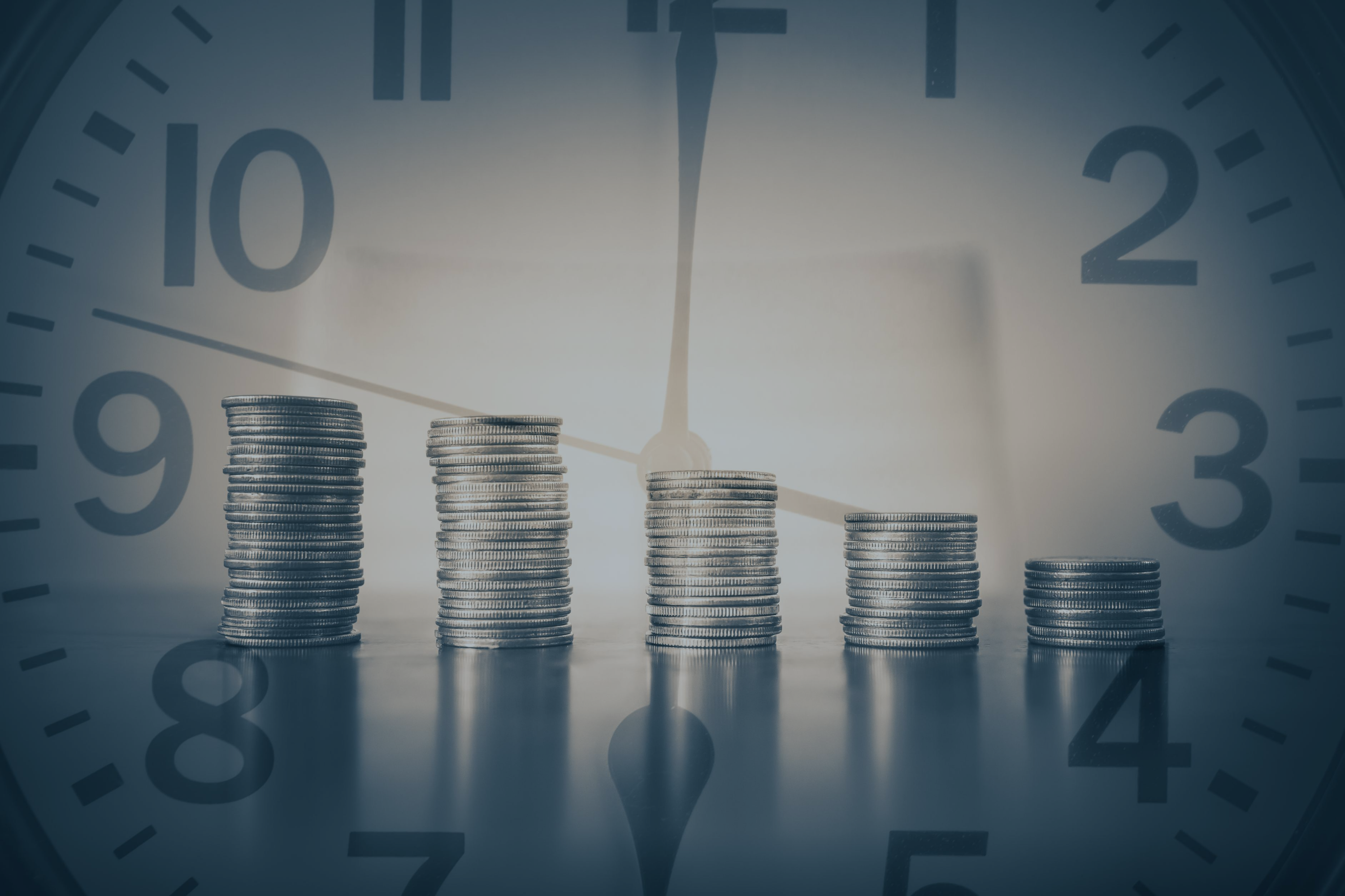 stacks_of_coins_in_front_of_a_clock_face_representing_time_and_cost