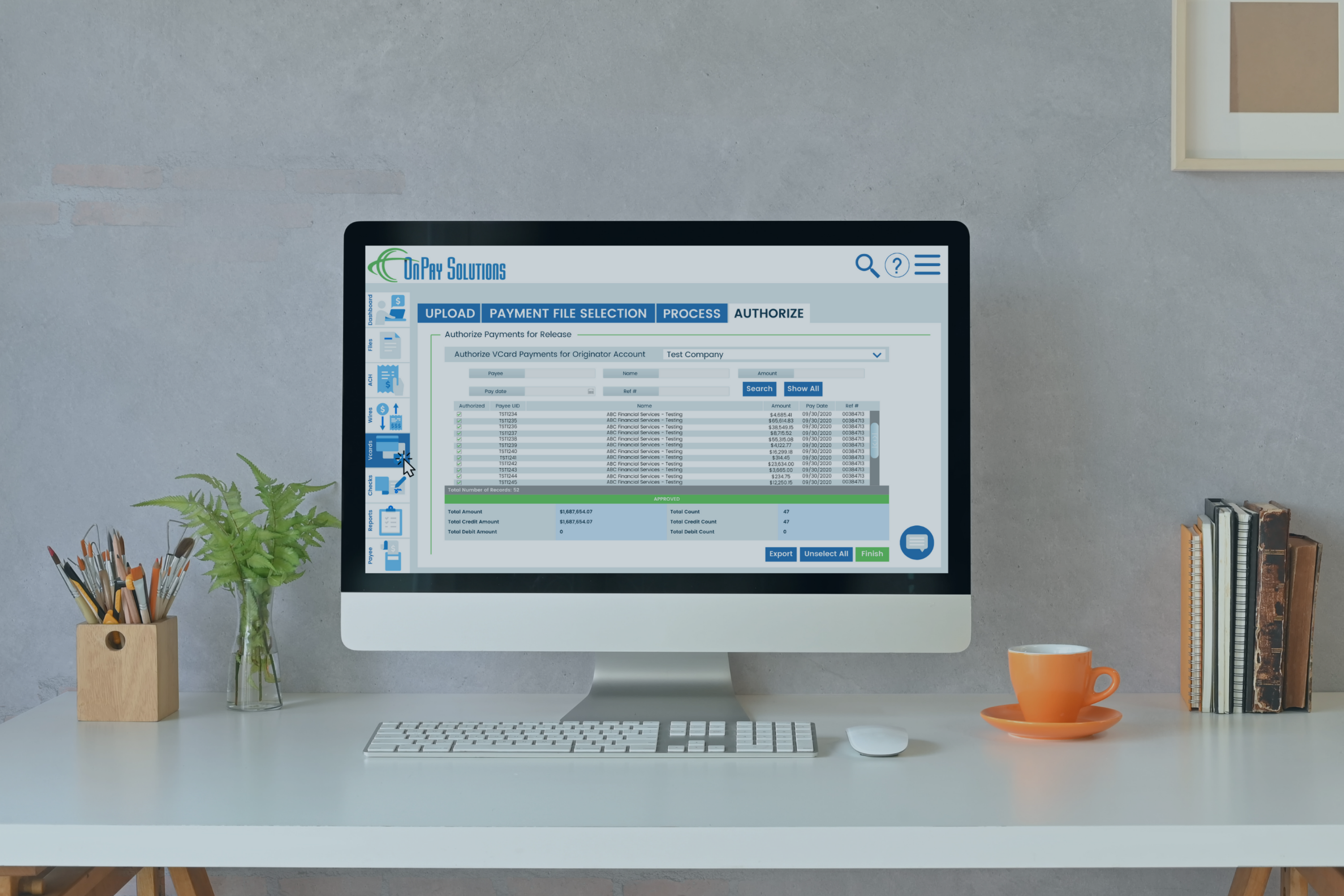 workspace_desktop_monitor_with_onpay_solutions_payment_portal_on_screen_with_books_and_coffee_cup_nearby