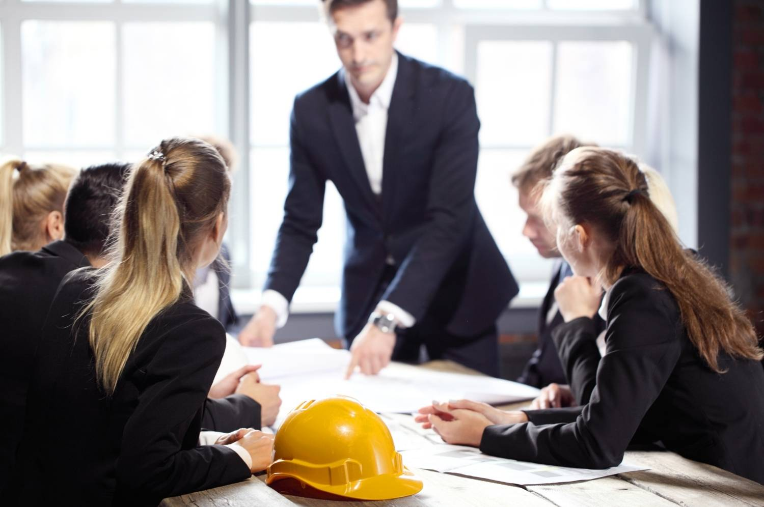 Business people group on meeting with constructin company looking at building blueprint