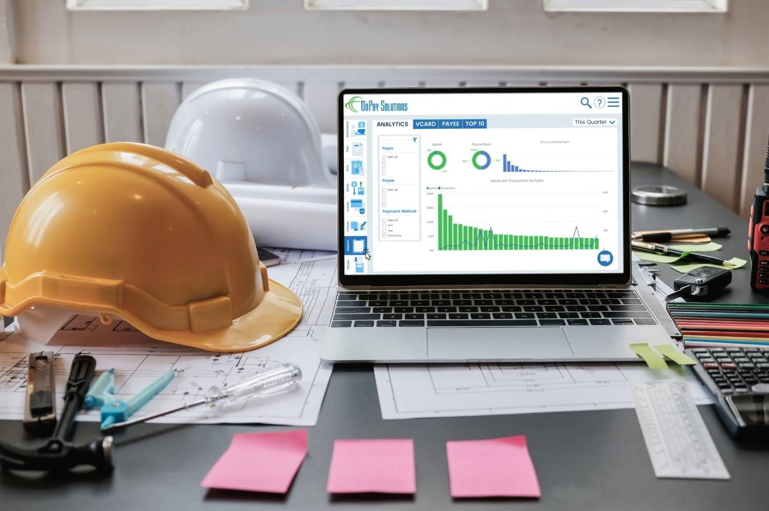 construction office desk with laptop displaying payment and invoice reporting on screen